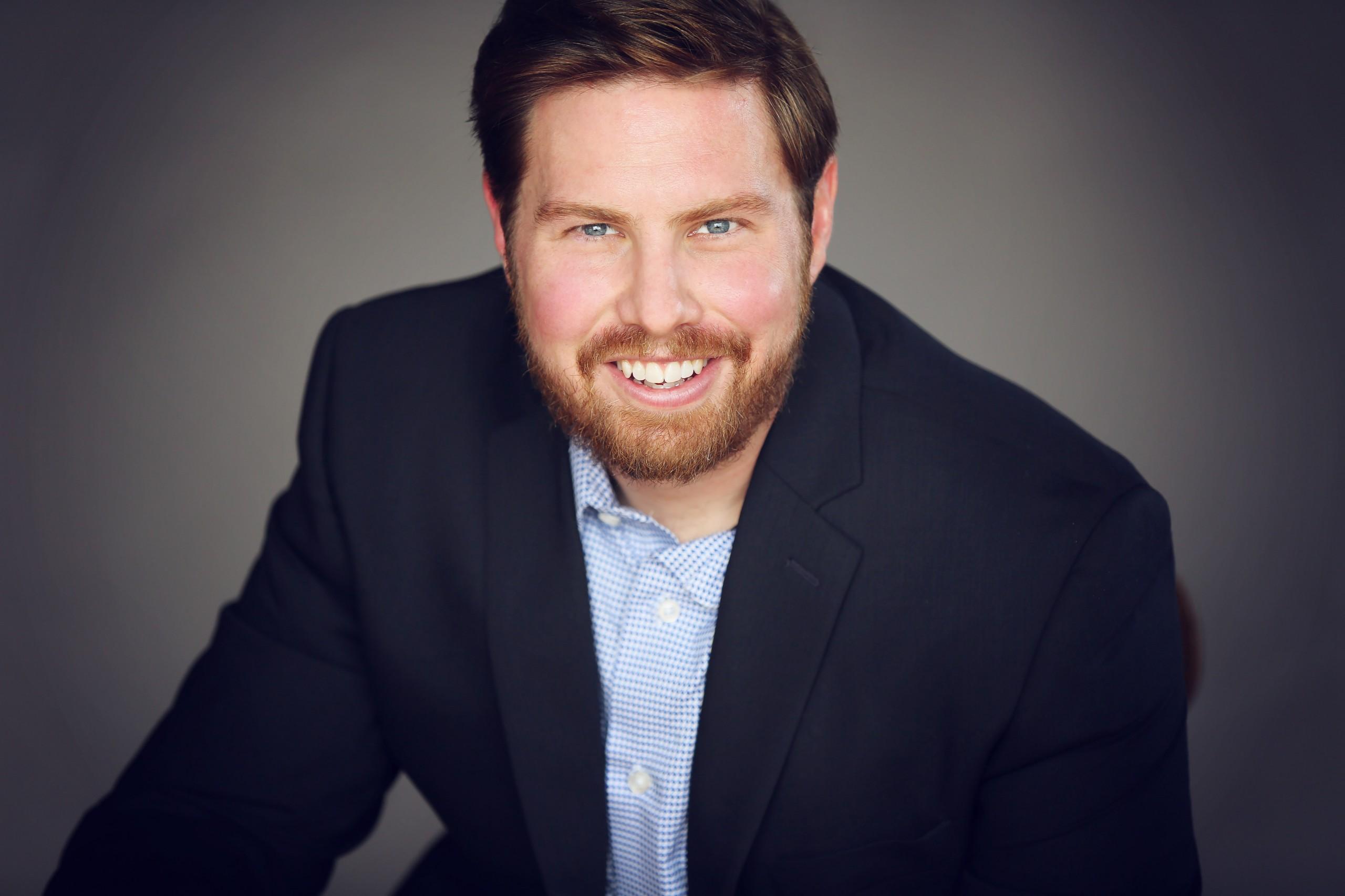 Portrait of Brian Winckel Blue Jacket Grey background